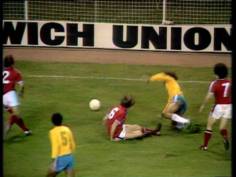 vídeos de stock, filmes e b-roll de brazil central defender edinho commits bad two-footed tackle on england full-back mick mills before feigning injury, england players protest about... - equipe esportiva