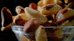 SLO MO LD Brazil nuts falling into a glass bowl