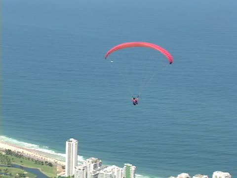 vídeos de stock e filmes b-roll de air to air, brazil, rio de janeiro, man paragliding above coastline - rio de janeiro