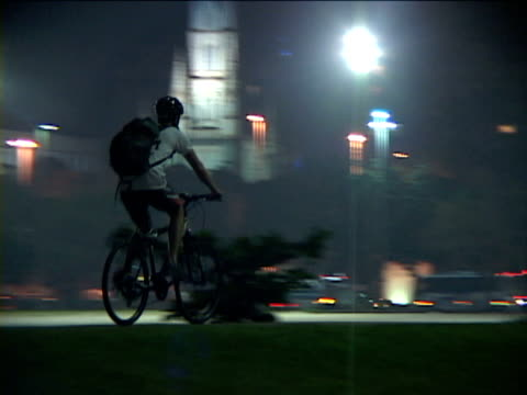vidéos et rushes de ms, ts, brazil, rio de janeiro, man riding bicycle on street at night, rear view - vélo ville