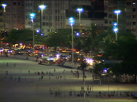ms, ha, brazil, rio de janeiro, people on copacabana beach at night, traffic on street in background - copacabana stock videos & royalty-free footage