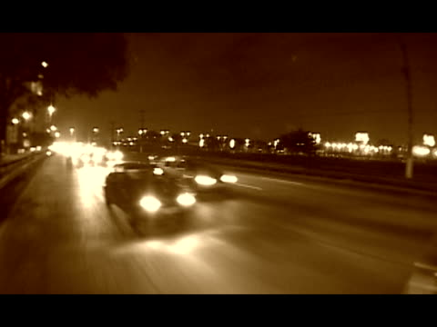 REAR/ SIDE POV, Brazil, Sao Paulo, Traffic on street at night, sepia toned