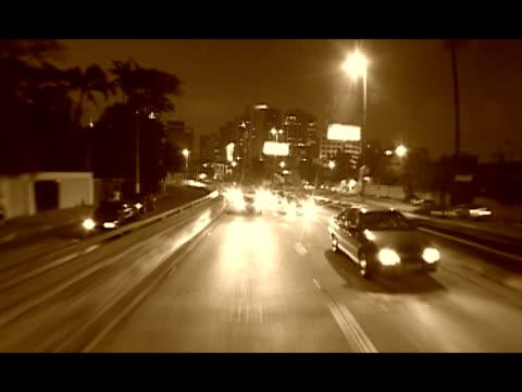 REAR POV, Brazil, Sao Paulo, Traffic on street at night, sepia toned