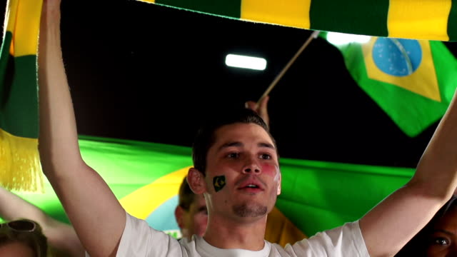 brazil sports fan / supporter holds up scarf (olympics) - fan enthusiast stock videos and b-roll footage