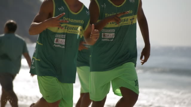 stockvideo's en b-roll-footage met brazilian athletes run on copacabana beach - uithoudingsvermogen