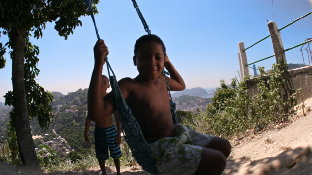 brazilian boy on swing smiles at camera as friend flaps arms behind him - rope swing stock videos & royalty-free footage