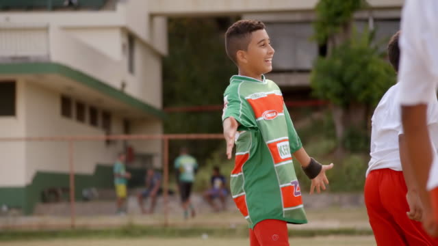 Brazilian boy raises his arms in mock protest in youth soccer scrimmage