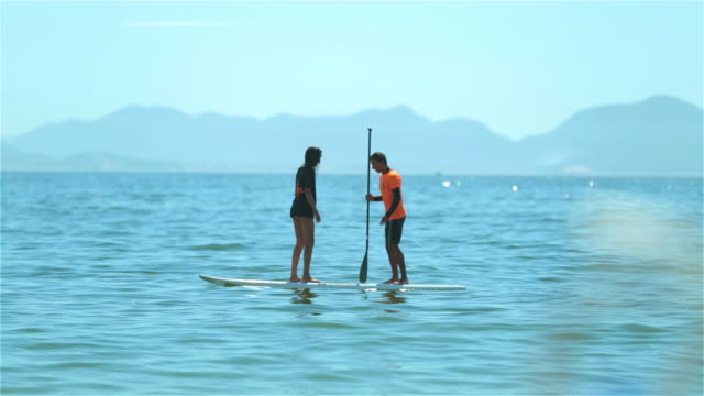 Brazilian boy shakes girl off paddleboard, loses balance and falls into the water off Copacabana Beach