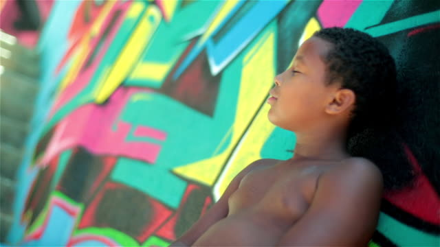 Brazilian boy turns and looks at camera leaning against graffitied wall in Rio slum