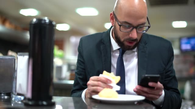 stockvideo's en b-roll-footage met braziliaanse business man eten pao de queijo - helemaal kaal