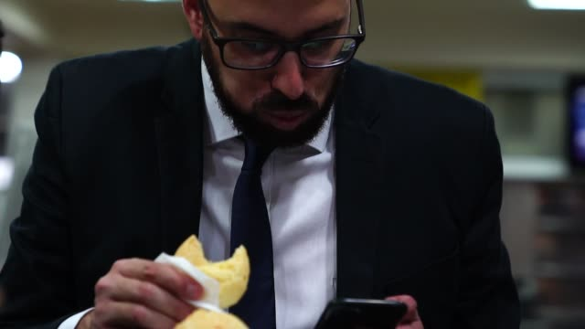 brazilian business man eating pao de queijo - cheese ball stock videos and b-roll footage