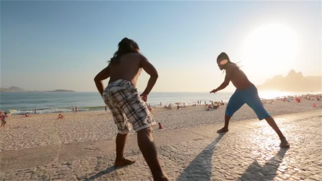 brazilian capoeira artists kick and dodge on ipanema beach boardwalk - martial arts stock videos & royalty-free footage