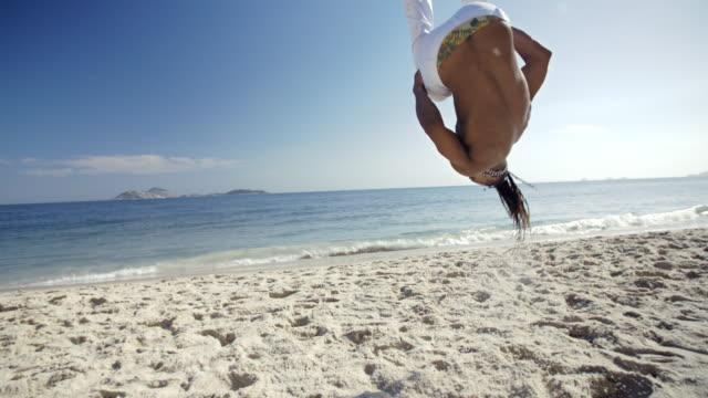 Brazilian capoeira fighter jumps and tucks his legs in an aerial flip on Ipanema Beach