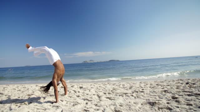 Brazilian capoeira fighter with dreadlocks flips backwards across Ipanema Beach