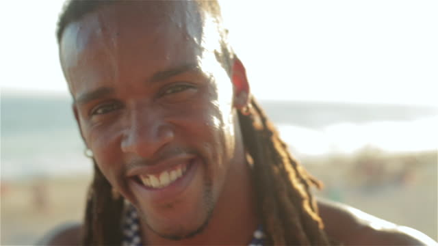 Brazilian capoeira fighter with dreadlocks smiles at camera