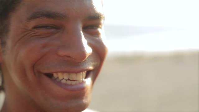 Brazilian capoeira martial artist smiles at camera on Ipanema Beach