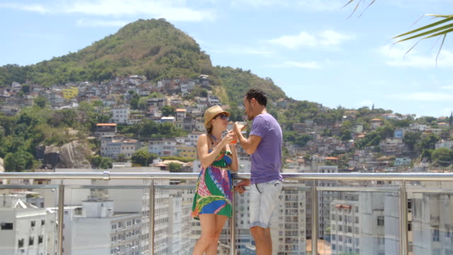 Brazilian couple chat intimately on hotel rooftop