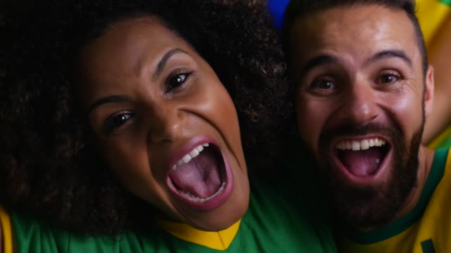 brazilian couple cheering with brazilian flag in the background - pardo brazilian stock videos & royalty-free footage