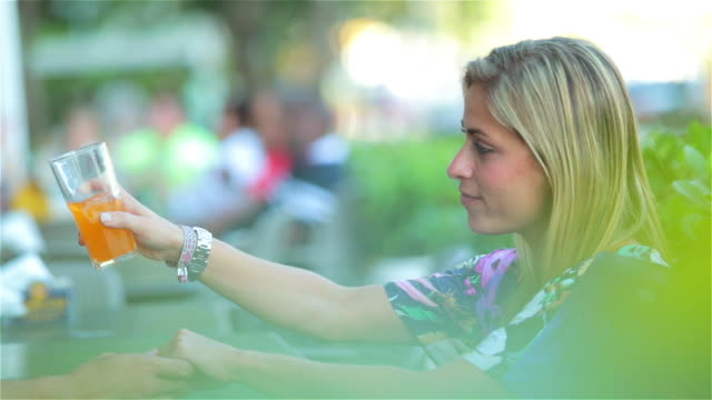 brazilian couple cheers glasses and drink together at outdoor restaurant - cola stock-videos und b-roll-filmmaterial