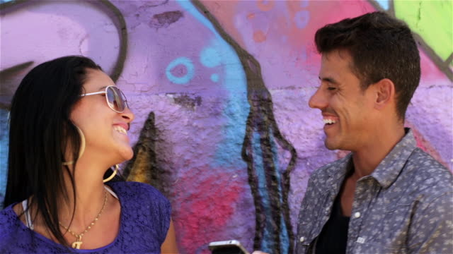 Brazilian couple leaning on graffitied wall chat and look at smartphone