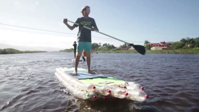 a brazilian couple makes stand up paddle boards out of discarded plastic bottles to clean up polluted beaches - südbrasilien stock-videos und b-roll-filmmaterial