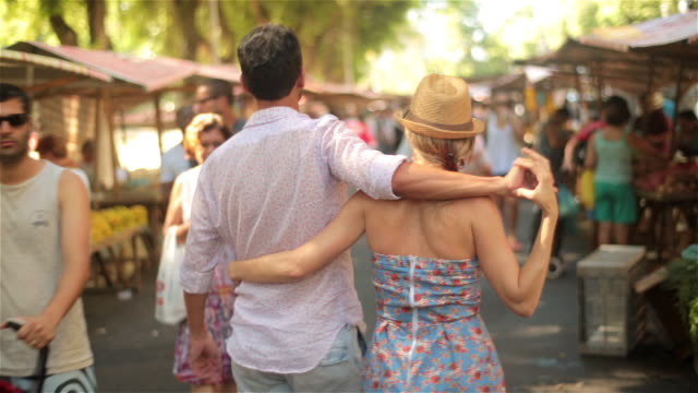 brazilian couple wrap arms around each other and hold hands walking through busy marketplace - urban road stock videos & royalty-free footage