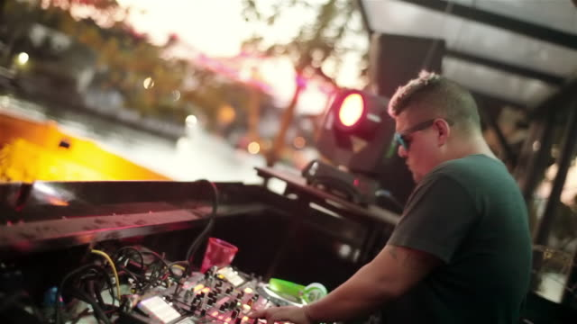 vídeos de stock, filmes e b-roll de brazilian dj grooves at soundboard while strobe lights flash at outdoor club - clubbing