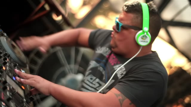brazilian dj spins digital turntable and takes off headphones - dj stock videos & royalty-free footage