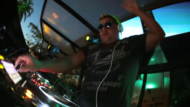 vídeos de stock e filmes b-roll de brazilian dj works soundboard and raises the roof at outdoor nightclub - luz estroboscópica
