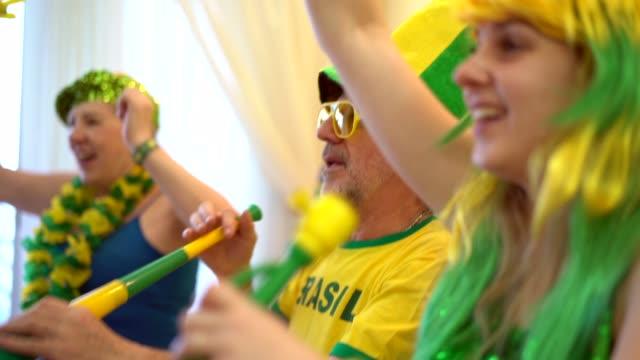 vídeos de stock, filmes e b-roll de família brasileira assistindo jogo de futebol em casa - competition round