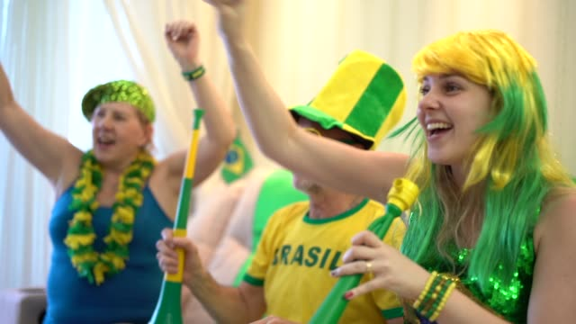Brazilian family watching soccer game at home
