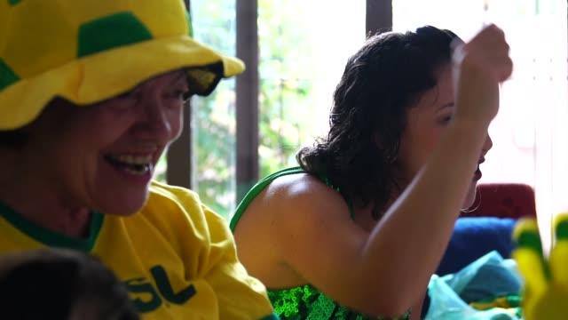 vídeos de stock, filmes e b-roll de fã brasileiro assistindo jogo de futebol em casa - competition round