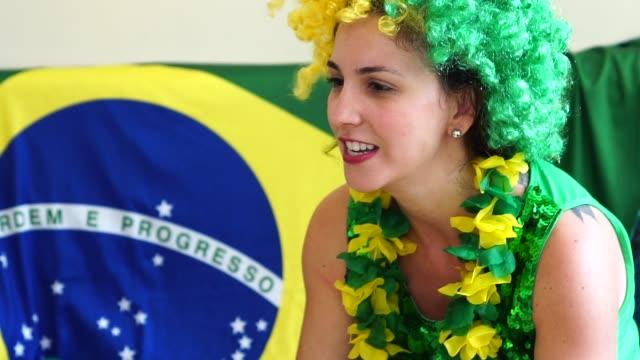 Brazilian fan watching soccer game at home