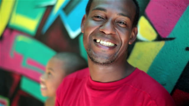 vídeos y material grabado en eventos de stock de brazilian father with children smiles at camera leaning on graffitied wall in rio - etnia latinoamericana e hispana