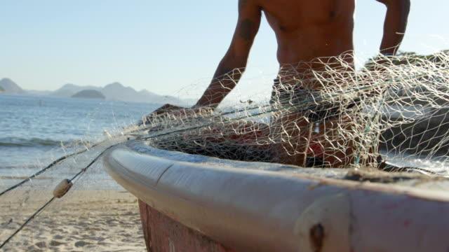 vídeos de stock, filmes e b-roll de brazilian fishermen pull fishing net onto boat on copacabana shore - puxando
