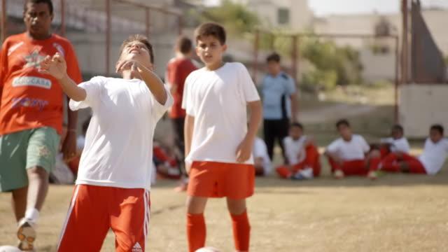 brazilian flag waves as boy heads soccer ball at youth league practice - geköpft stock-videos und b-roll-filmmaterial