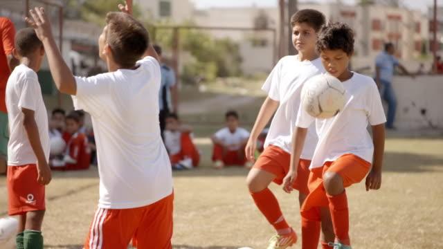 Brazilian flag waves as youth soccer team practice juggling soccer balls