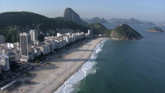 vídeos de stock, filmes e b-roll de a brazilian flag waves in the wind on a hill overlooking the ocean and the many skyscrapers of rio de janeiro. - formato de alta definição