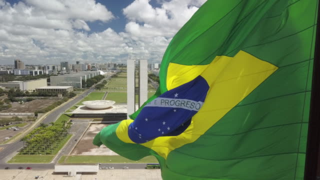 brazilian flag with brasilia cityscape and parliament in background - brazil stock videos & royalty-free footage