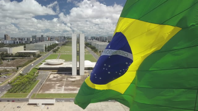 vídeos de stock, filmes e b-roll de brazilian flag with brasilia cityscape and parliament in background - parliament building
