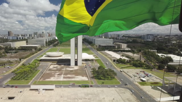 ts brazilian flag with brasilia cityscape and parliament in background - brasilia stock videos and b-roll footage