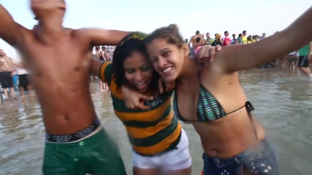 brazilian football fans, show their support of the brazilian national football team on a beach in rio de janeiro, on june 30th, 2014. - national team stock videos & royalty-free footage