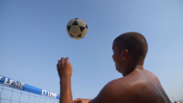 brazilian footvolley player leaps into the air to head soccer ball over net - trefferversuch stock-videos und b-roll-filmmaterial