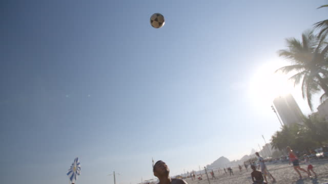 brazilian footvolley player shoulders ball into the air for his partner to head it over the net in slow motion - internationaler fußball stock-videos und b-roll-filmmaterial