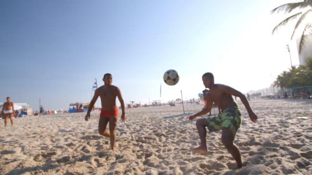 brazilian footvolley team trap, set, and head soccer ball over net on copacabana beach - internationaler fußball stock-videos und b-roll-filmmaterial