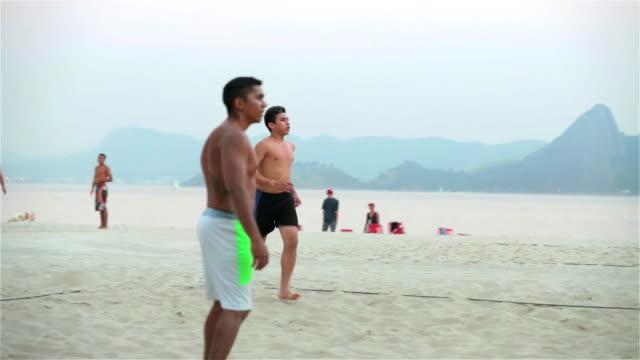 brazilian footvolley teammates serve ball and return volleys on botafogo beach - internationaler fußball stock-videos und b-roll-filmmaterial