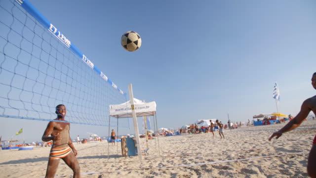 brazilian footvolley teams kick and head soccer ball back and forth over net on copacabana beach - internationaler fußball stock-videos und b-roll-filmmaterial