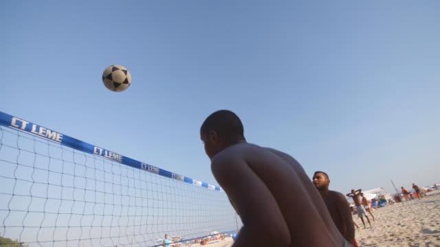 brazilian footvolley teams kick and head soccer ball back and forth over net in intense beach match - internationaler fußball stock-videos und b-roll-filmmaterial