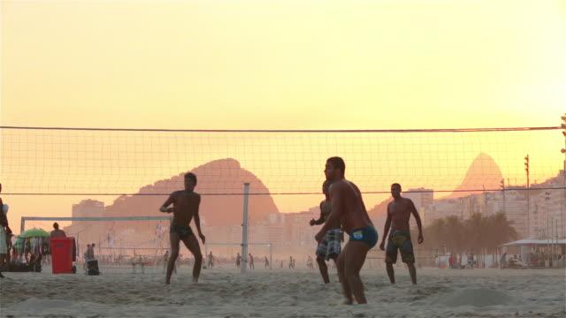 vídeos de stock, filmes e b-roll de brazilian footvolley teams send soccer ball back and forth over net on copacabana beach - send