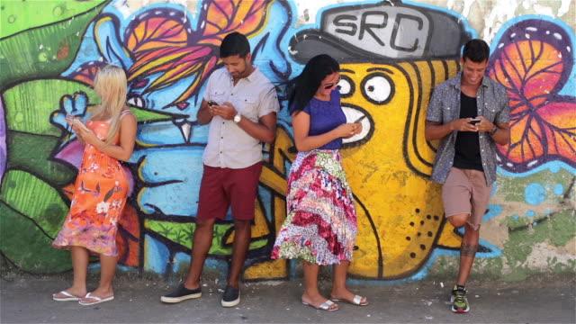 vidéos et rushes de brazilian friends lean against graffitied wall and text on smartphones - manque